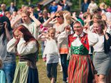 Sunnansj?, Sweden - June 20, 2015: Men, women and children, some in traditional folk customes, dancing around a maypole at a traditional swedish midsummer celebration. The song and dance performed here is the traditional Sm? grodorna, or The Little Frogs in english.